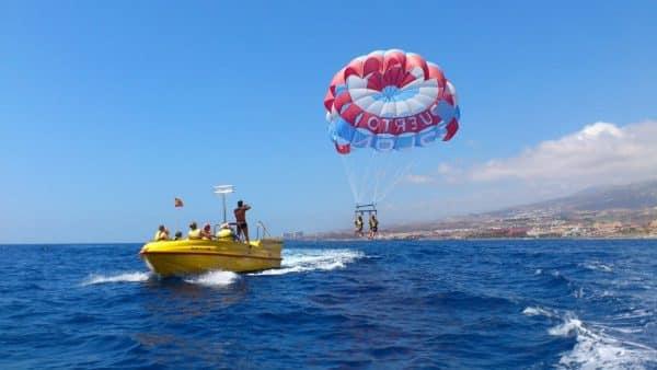 2 personas volando en el aire durante una excursión de parascending en Tenerife, y el guía de la embarcación hace fotos