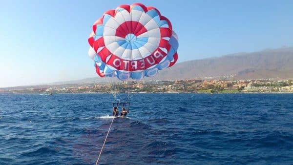 pareja disfrutando del parascending cerca de Puerto Colón y tocando el agua con los pies