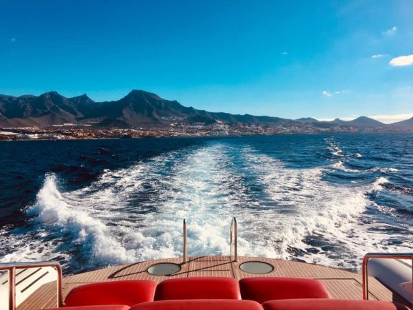 Backside of luxury yacht with Costa Adeje and playa de las americas in the background
