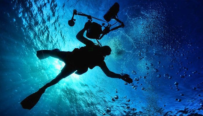 Man is diving and holding a camera