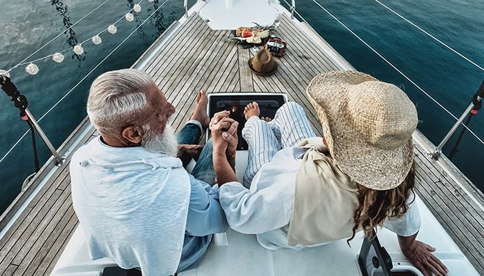 couple hold hands in front of boat