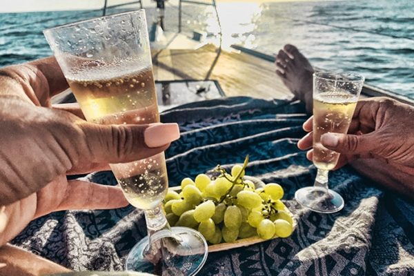 people drinking cava and eating grapes in front of a boat
