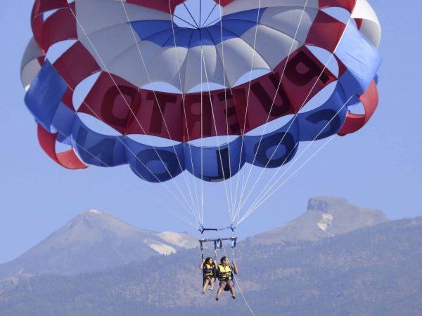 2 personas volando alto durante un viaje de parascending con el volcán Teide de fondo