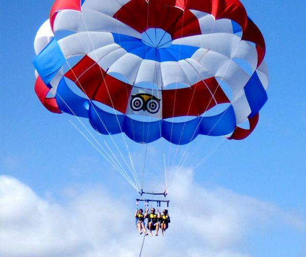 3 personas volando sobre el agua de las americas en Tenerife durante un viaje en parasailing