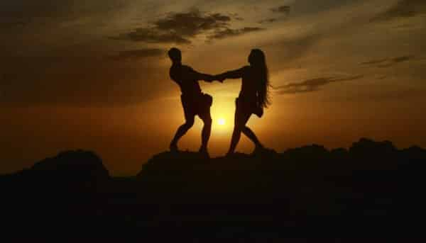 Girl and boy hold hands during sunset