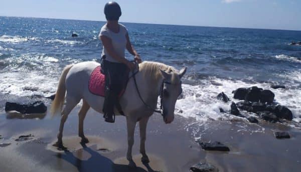 Woman on a horse near a beach in Tenerife