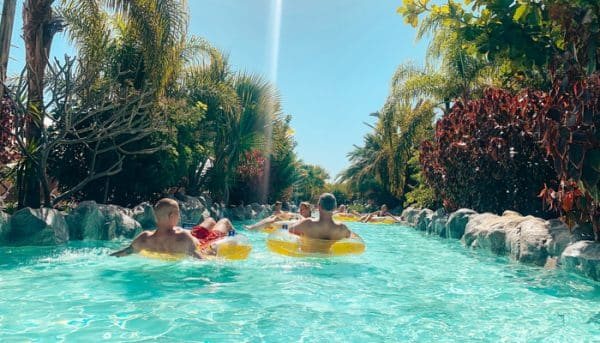 People relaxing on bands on the lazy river of water park Siam Park