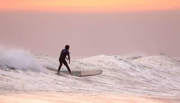 Boy surfing during sunset
