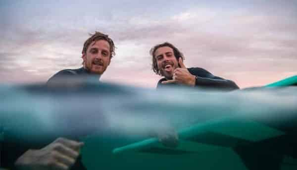 2 guys on the ocean have a break while surfing