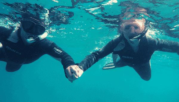 Toeristen op een snorkelexcursie houden elkaars hand vast