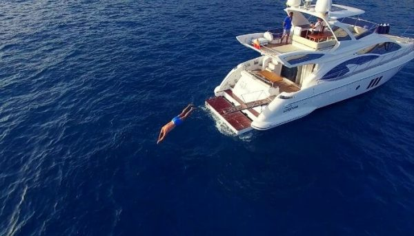 Man jumping into water during private boat trip