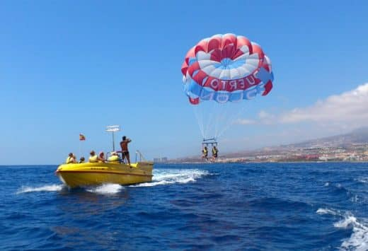 2 people flying in the air during a parascending trip in Tenerife, and the guide on the boat takes photos